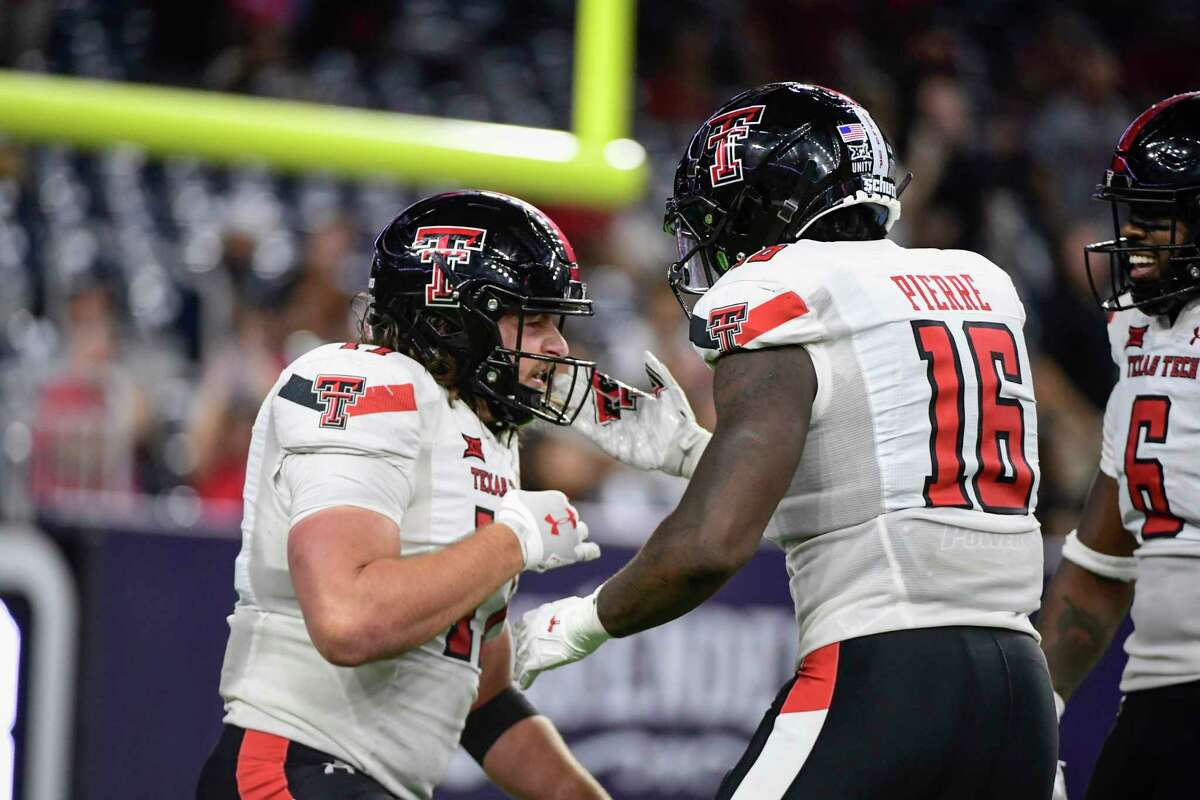 Texas Tech linebacker Colin Schooler (17) and linebacker Jesiah Pierre (16) celebrate a tackle by Schooler against Houston during the second half of an NCAA college football game Saturday, Sept. 4, 2021, in Houston. (AP Photo/Justin Rex)