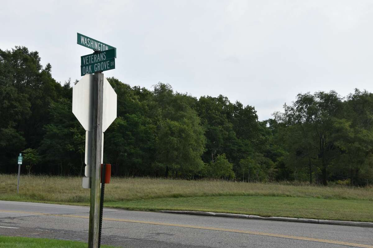 A street sign adjacent to an empty patch of grass at Washington Street and Veterans Oak Grove Drive shows the location for the proposed Lake Winds Apartment