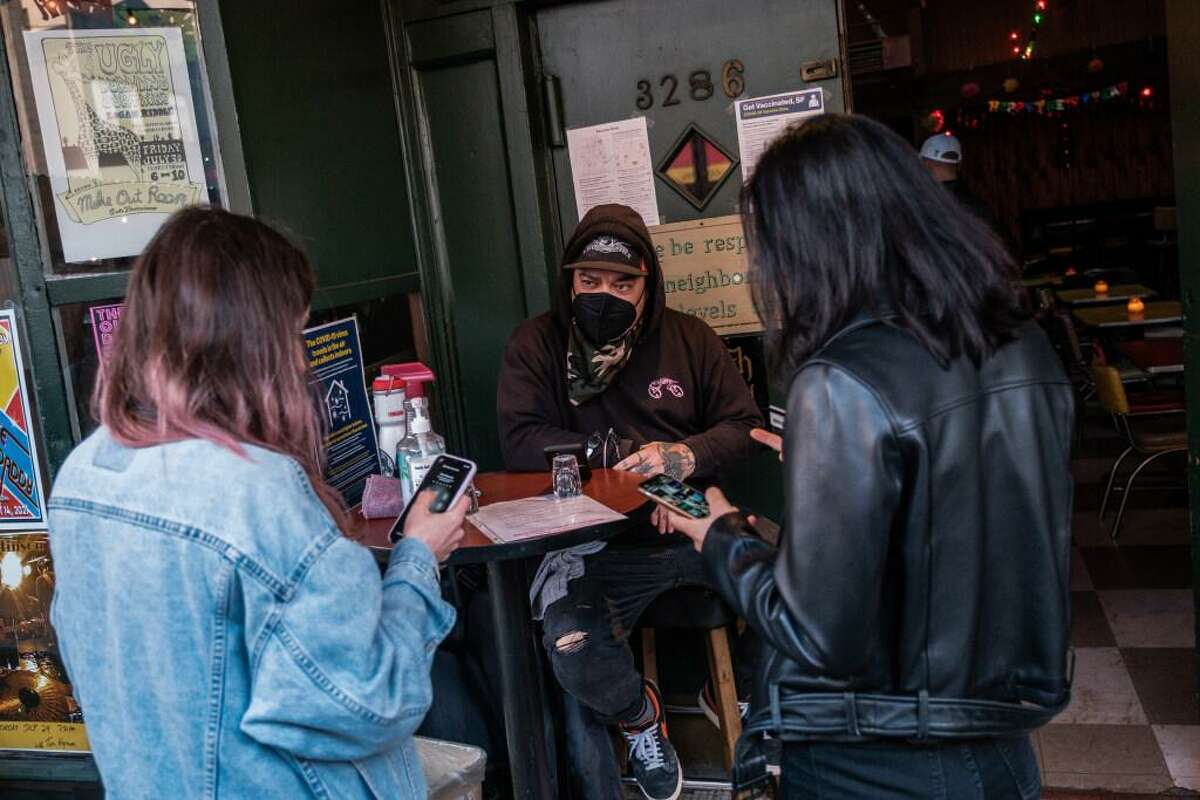 Doorman Jason Voisine waits for two patrons to show him proof of vaccination at the Latin America Club in San Francisco on Thursday, July 22, 2021. The Latin American Club is one of many bars and restaurants in the city that are now requiring proof of vaccination before entering.