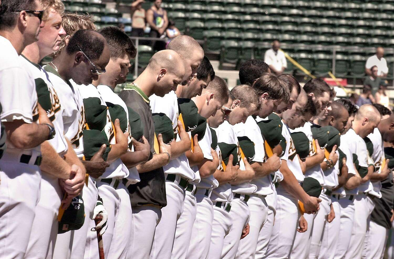 Members of the Oakland Athletics baseball team are lined up side by side, and stand with their heads bowed before a 2001 game.