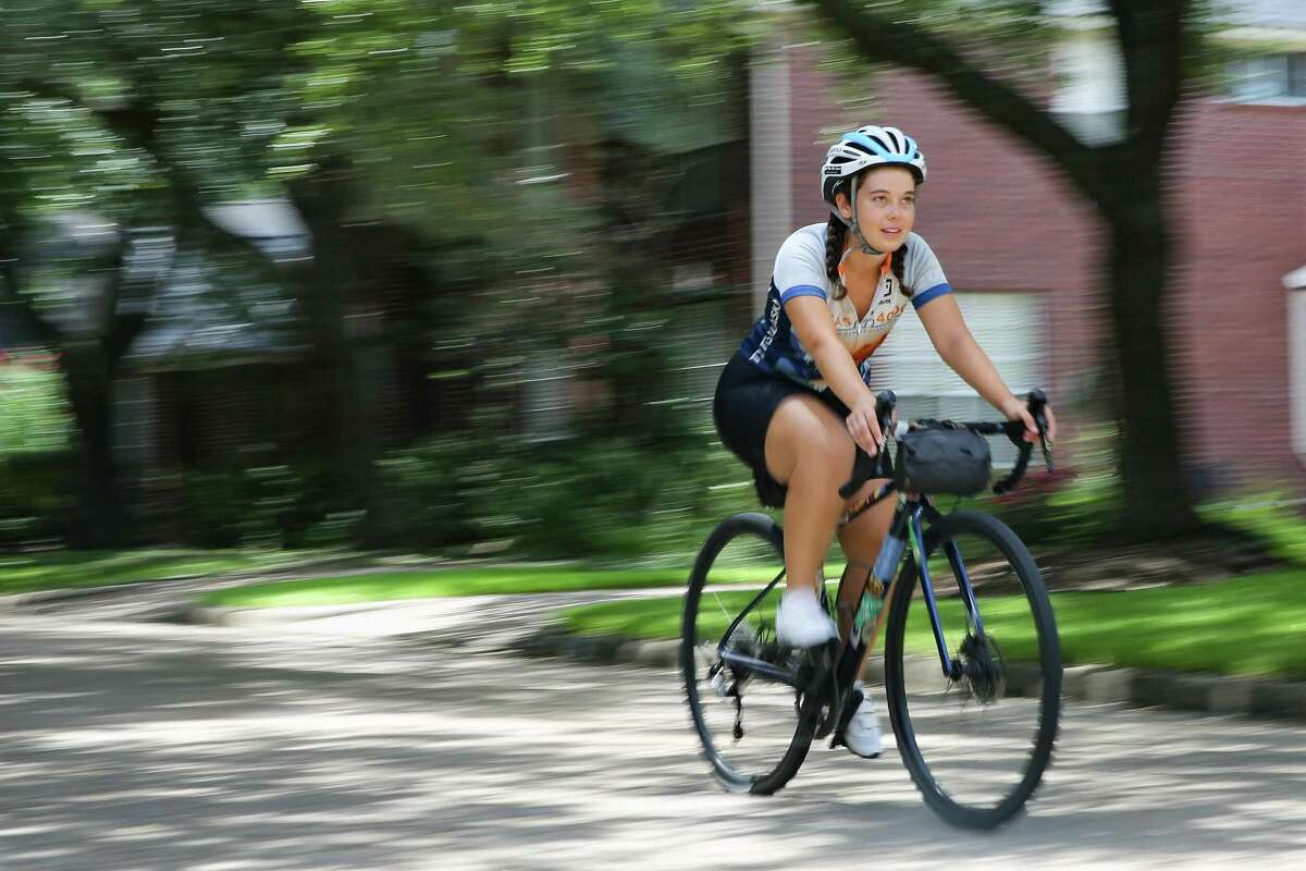 Lilian Velez, 23, rides her bicycle on her street in Houston on Friday, Aug. 20, 2021. Velez survived ovarian cancer at age 13. She just returned a bike ride across the U.S. to raise money for cancer.