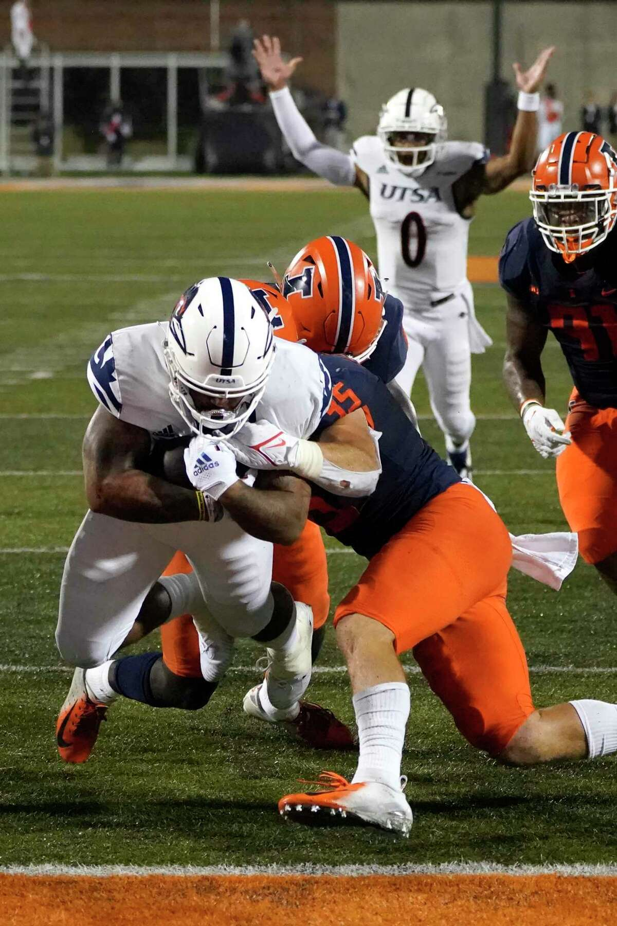 UTSA running back Brenden Brady, left, scores as Illinois linebacker Jake Hansen (35) defends during the first half of an NCAA college football game Saturday, Sept. 4, 2021, in Champaign, Ill. (AP Photo/Charles Rex Arbogast)
