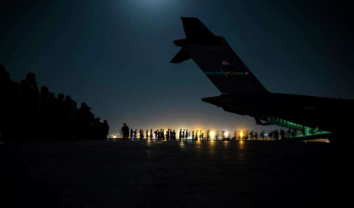In this Saturday, Aug. 21, 2021 photo provided by the U.S. Air Force, aircrew assigned to the 816th Expeditionary Airlift Squadron assist qualified evacuees boarding a U.S. Air Force C-17 Globemaster III aircraft in support of the Afghanistan evacuation at Hamid Karzai International Airport, Kabul, Afghanistan. (Senior Airman Taylor Crul/U.S. Air Force via AP, File)