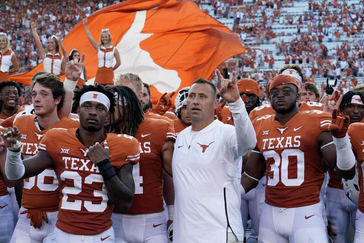 Texas head coach Steve Sarkisian, center, stands with players for the school song following an NCAA college football game against the Louisiana-Lafayette, Tuesday, Sept. 7, 2021, in Austin, Texas. (AP Photo/Eric Gay)