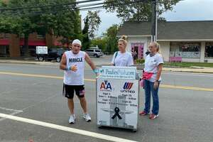 """Paul """"Paulie"""" Veneto poses for a picture with his beverage cart in Darien along his journey from Logan Airport in Boston to ground zero in New York City. The walk honors those killed on 9/11 20 years ago."""