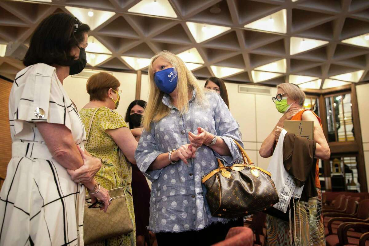 Congregation Fates of Prayer member JoAnn Katz, center, chats with other evacuees after attending a Rash Hashanah service at Congregation Emanu El in Houston on Tuesday, Sept. 7, 2021.