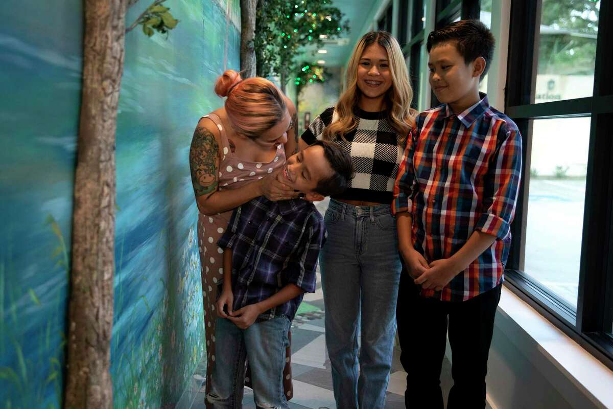 Vanessa Ibarra and her three children, Mia, Joshua and Yurjah stand in the Peaceful Pathway at The Children's Bereavement Center of South Texas. The center, which has recently expanded, helped the children in dealing with the loss of their father last year.