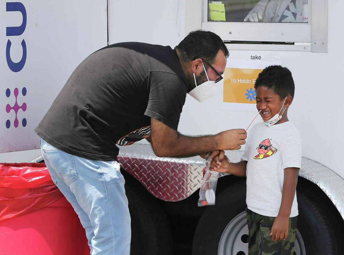 Rodolfo Sifuentes performs a nasal swab test on his 5-year-old son, Gabriel, who Sifuentes said showed some possible symptoms. They were amongst other people getting tested at the Curative mobile testing site at the American Legion Alamo Post #2 on Fredericksburg Road on Friday, Sept. 3, 2021.