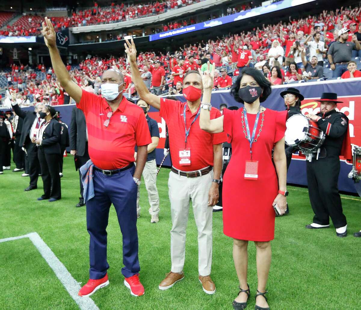 UH chancellor Renu Khator, with husband Suresh, center, and Mayor Sylvester Turner during the school's football season opener Saturday, has led the university on a meteoric rise in nearly 14 years.