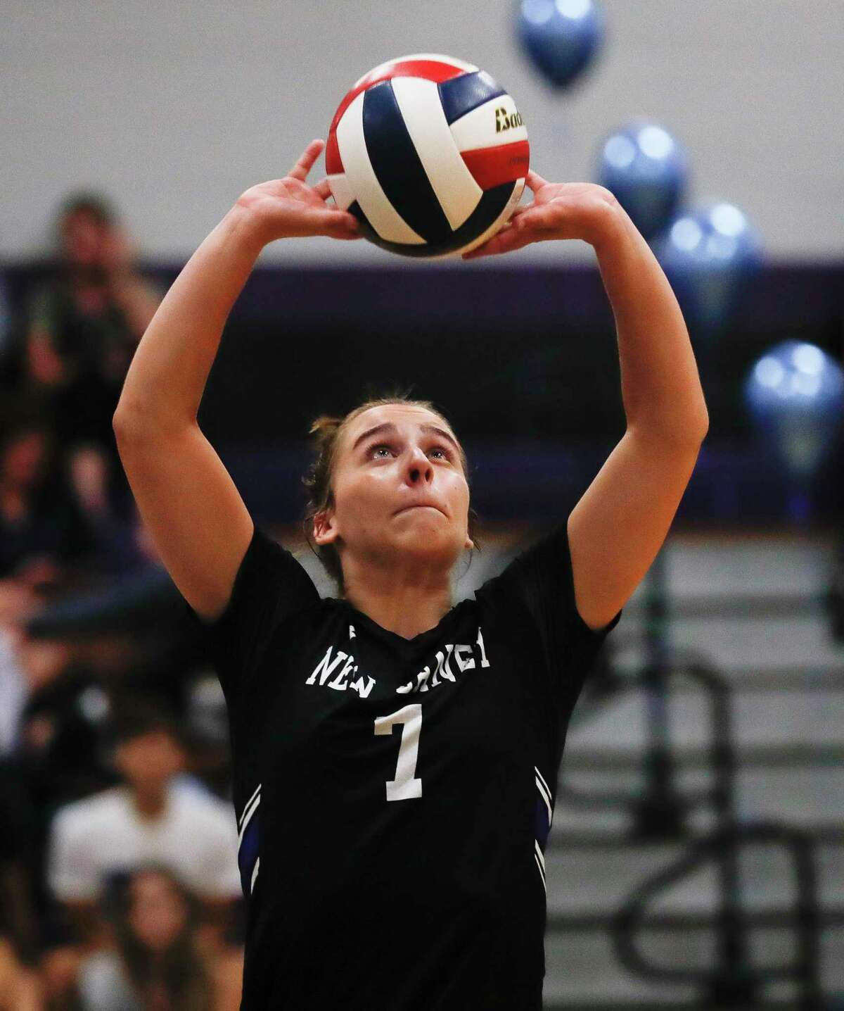 New Caney's Lily Thompson (7) sets the ball during the second set of a high school volleyball match at Willis High School, Tuesday, Sept. 7, 2021, in Willis.