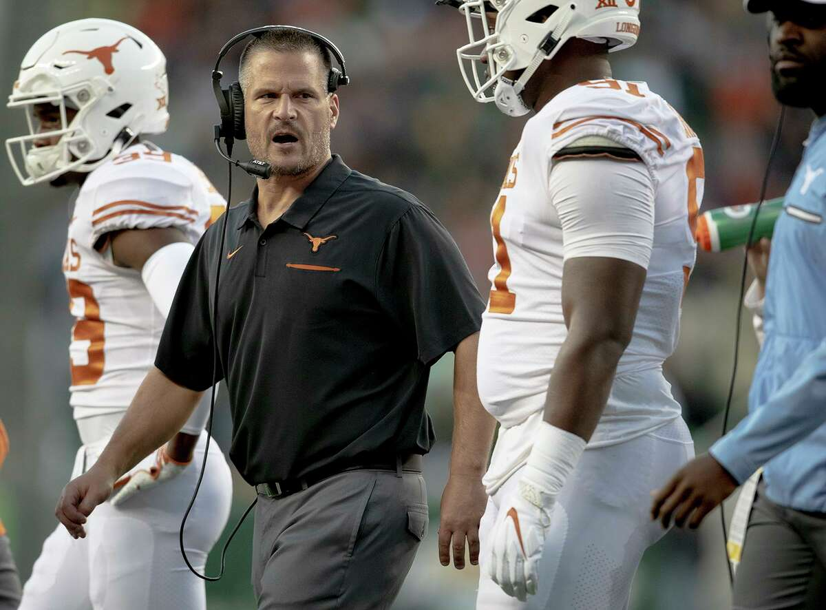 Texas defensive coordinator Todd Orlando, second from left, talks with his players during an NCAA college football game against BaylorSaturday, Nov. 23, 2019, in Waco, Texas. (Nick Wagner/Austin American-Statesman via AP)