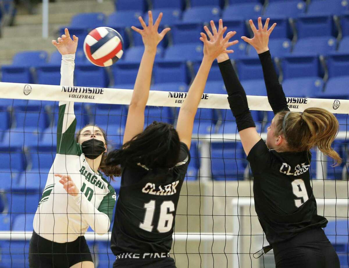 Reagan's Erin Jones (10) attempts to hit around Clark's Sofia Scheuerman (16) and Kendall Harrington (09) in girls volleyball at Northside Gym on Tuesday, Sept. 7, 2021. The Rattlers defeated the Cougars, 3-1 in sets, to take the matchup.