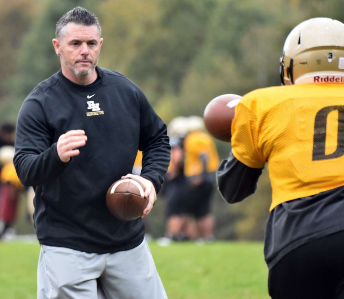 East Hartford coach Rick Milton snaps the ball during practice on Monday, Oct. 22, 2018.
