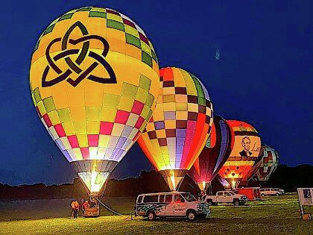 Balloons light up the night sky in September 2020 in Macomb during the Macomb Balloon Rally's drive-through balloon glow. The event, which was scaled back in 2020 because of pandemic restrictions, will go on as usual this weekend.