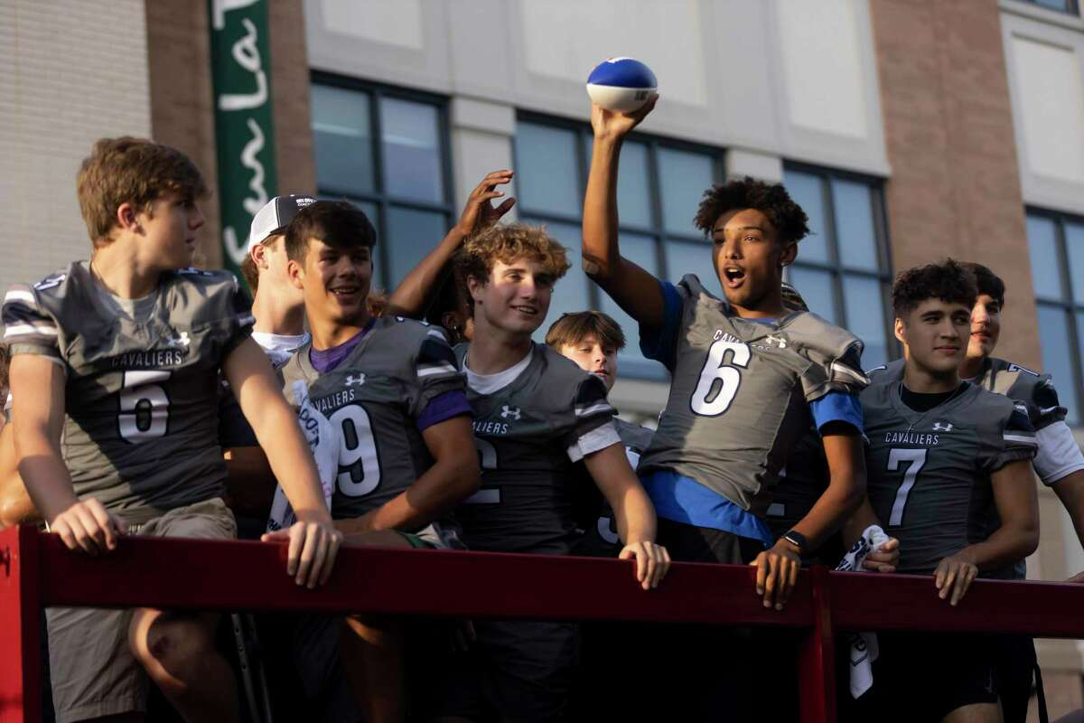 The Woodlands College Park varsity players wave to the crowd from the top of a truck during College Park High School's homecoming parade and prep rally at Market Street, Tuesday, Sept. 7, 2021, in The Woodlands. Hundreds of supporters and family filled Central Park at Market Street during the rally and parade.