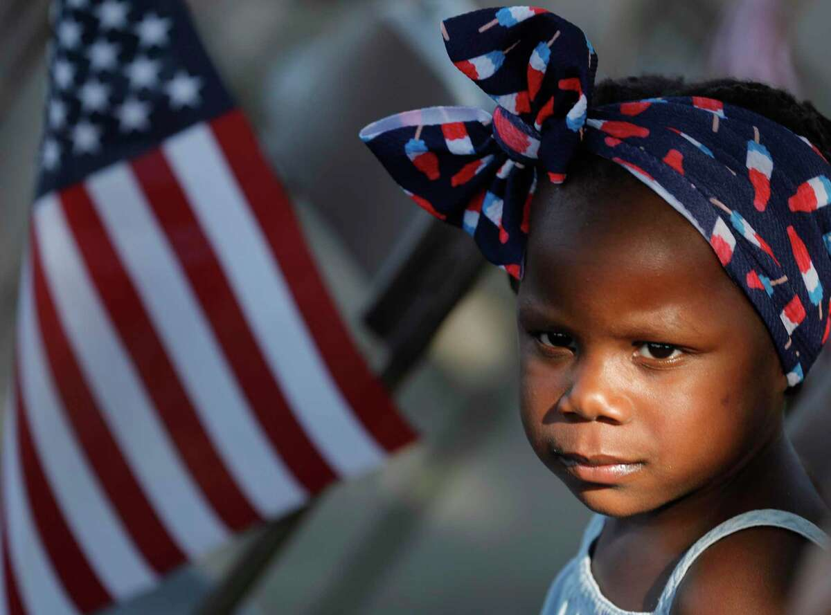 Ariana, whose parents declined to give her last name, is seen wearing a a colorful headband as community members gathered at the Montgomery County War Memorial Park to honor the 13 U.S. soldiers who died during an Aug. 6 attack at the Kabul airport in Afghanistan.