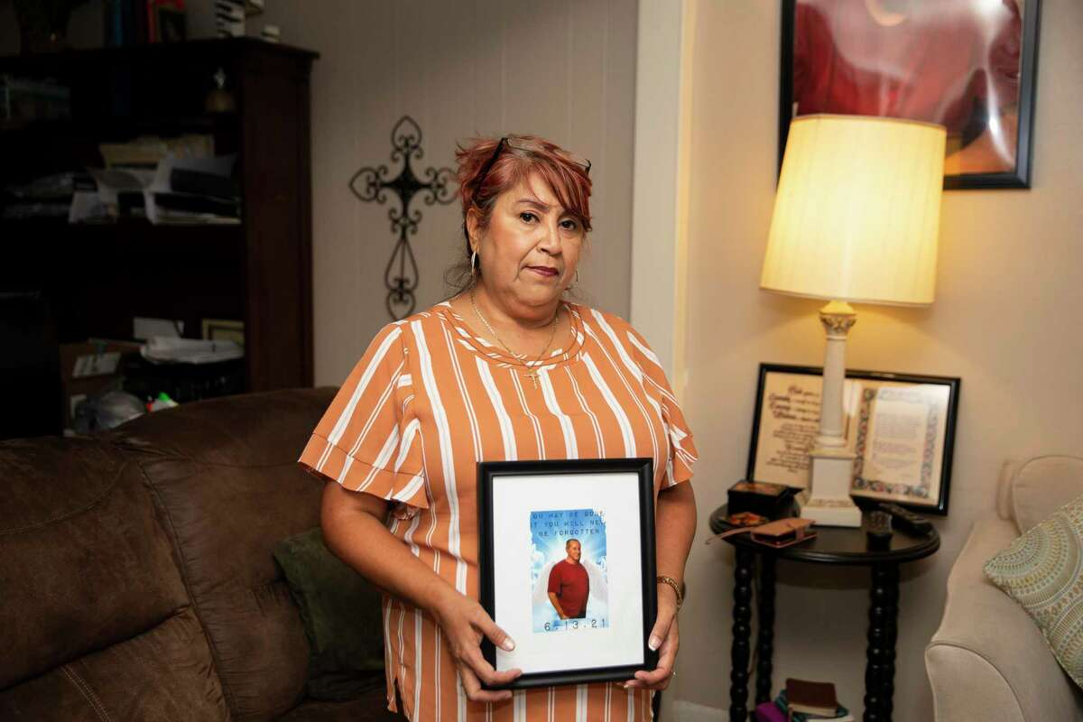 Esmeralda Trigo poses with a photograph of her brother, Albert Ramirez, on Tuesday, Aug. 24, 2021 at her Rosenberg home. Ramirez died in June in the custody of the Fort Bend County sheriff's office after being jailed for 16 months on an aggravated robbery charge. Preliminary autopsy results show he died from natural causes, including cirrhosis of the liver. However, his family has hired a lawyer and is questioning whether he received the right medical care.