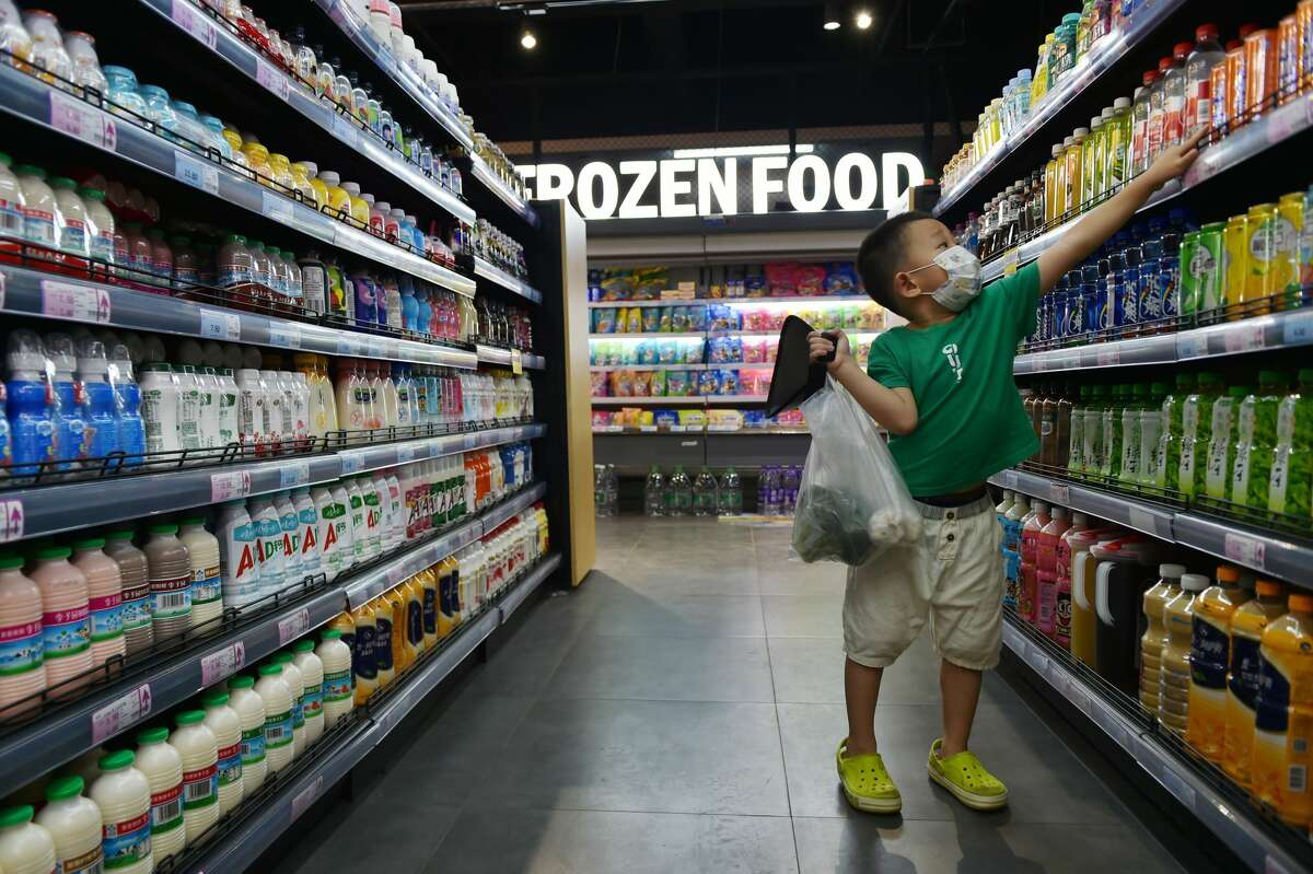 FILE- A boy shops in a supermarket in Nanjing in east China's Jiangsu province Monday, Aug. 09, 2021. (Feature China/Barcroft Media via Getty Images)