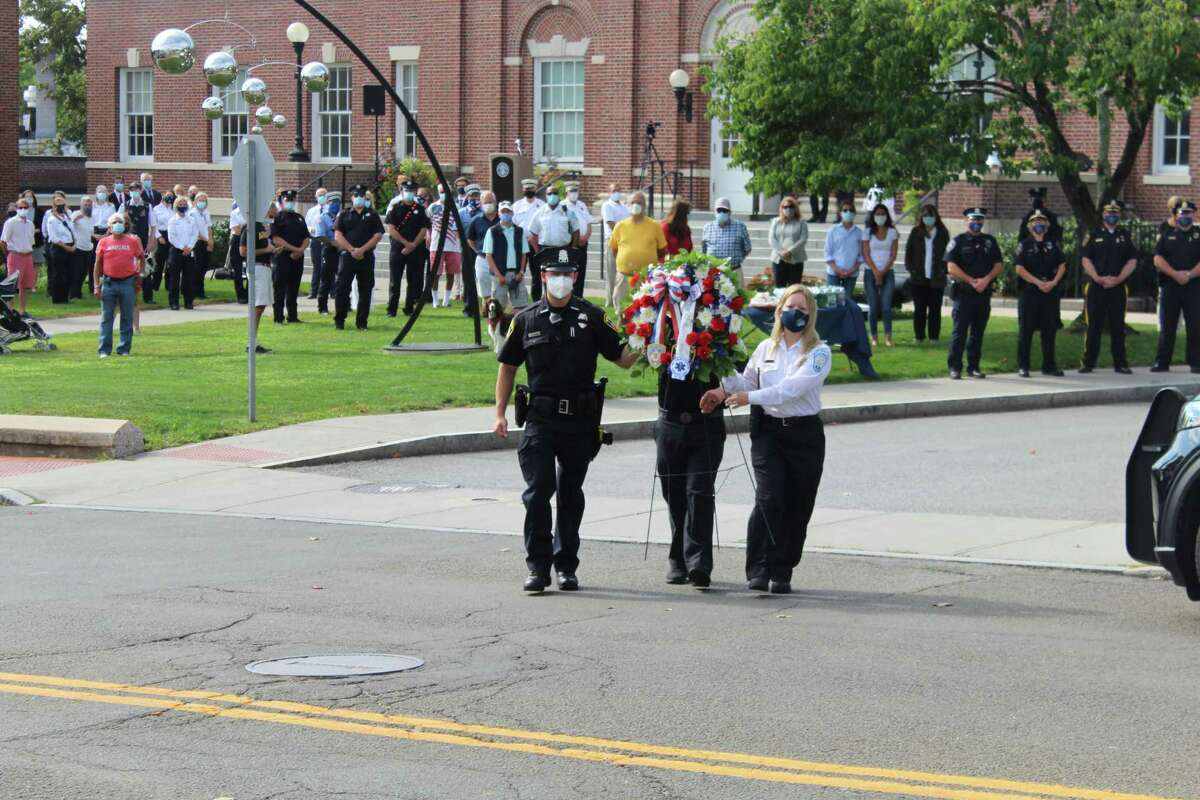 New Canaan first responders carry a wreath in memory of those who lost their lives of Sept. 11, 2001, across Main Street to the memorial in front of the New Canaan Fire Department during Friday's observance of the 19th anniversary of the terrorist attacks.