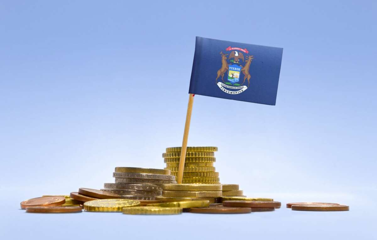 FILE - Flag of Michigan in a mixed stack of coins.