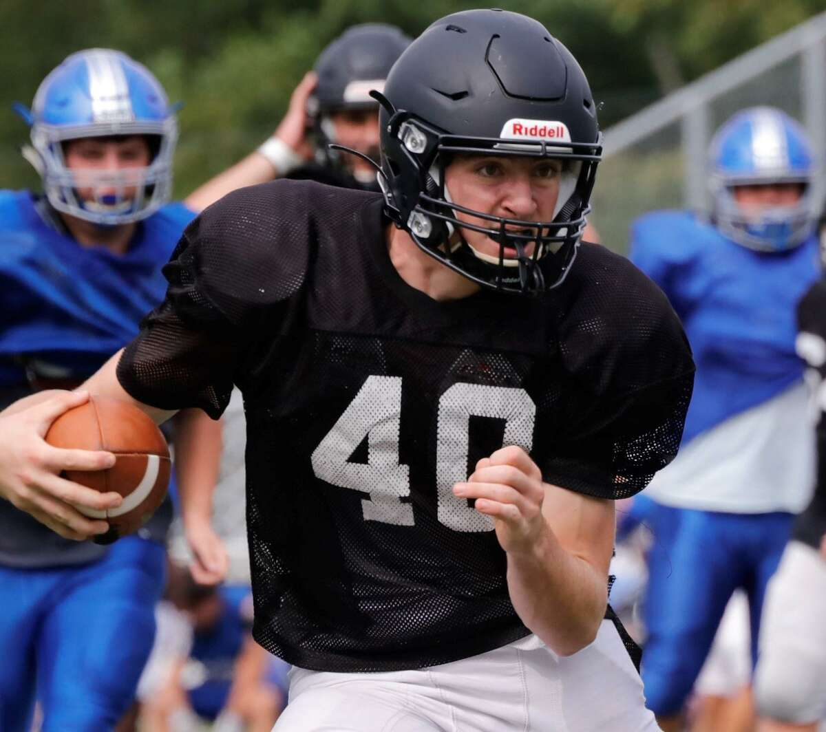 Law's Lucas Pincus-Coyle runs the ball during scrimmage with Bunnell. Spencer Hannon, John Neider and Pincus-Coyle are team captains.