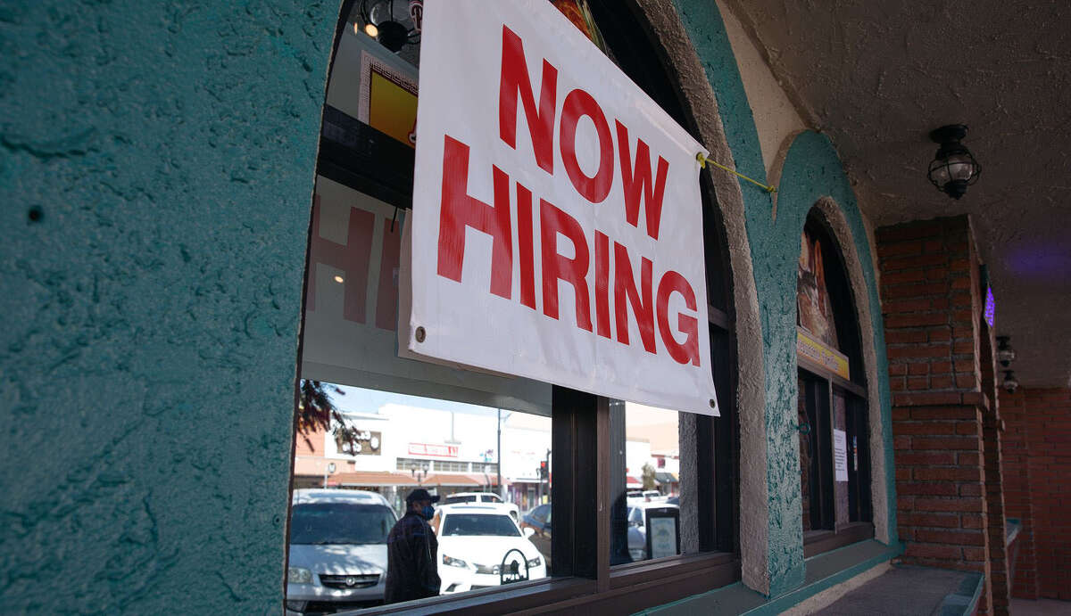 """A """"Now Hiring"""" sign outside a restaurant in Huntington Park, Calif., on March 24, 2021."""