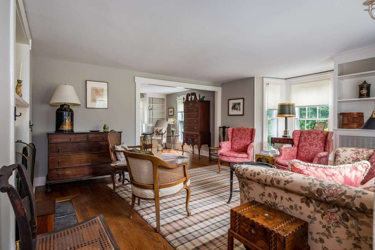 The living room in the home on 524 Boston Post Road in Madison, Conn. has a fireplace and period details throughout.