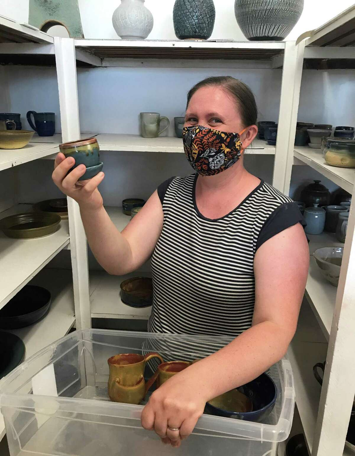 Suzanne Greenwald, a co-op member at Wesleyan Potters in Middletown, picks up her pottery after a glaze firing last summer.