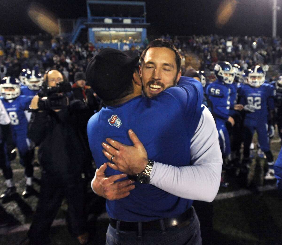 Southington coach Mike Drury gets a congratulatory hug after Southington beat Fairfield Prep, 52-34, to win the 2013 Class S state championship on December 19, 2013.