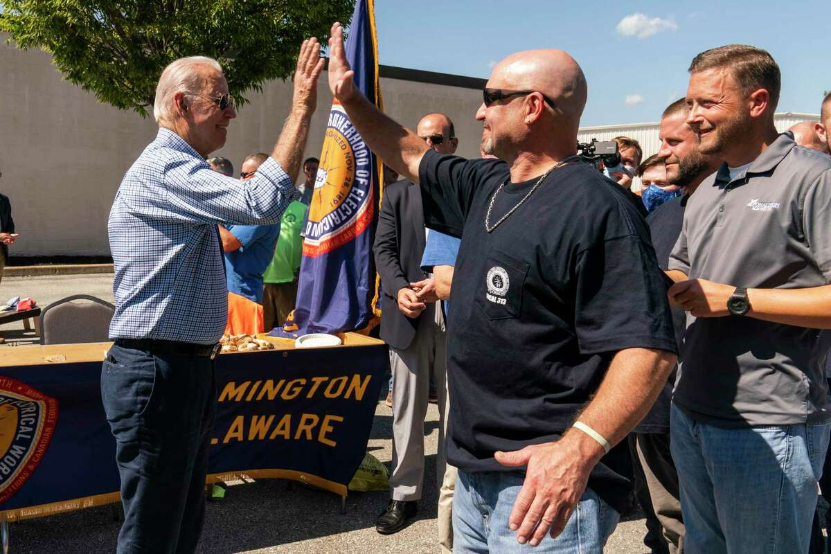 President Joe Biden gets a high-five from a member of the International Brotherhood of Electrical Workers on Labor Day, but his popularity overall has plunged in recent weeks, reflecting these partisan times.