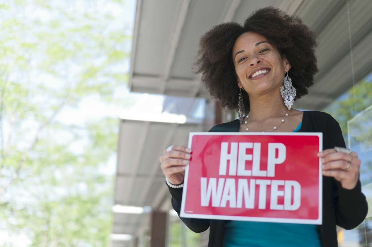 FILE - A business woman holds a help wanted sign outside of a store front in Grand Rapids, Michigan.