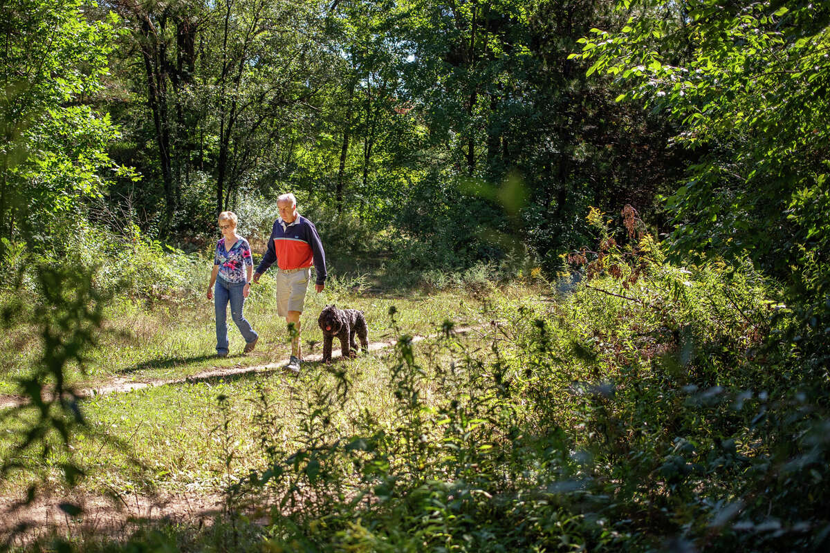 Sharon Berkan-Dent, left, and Stan Dent, right, enjoy a walk with their dog, Zoey, Wednesday, Sept. 8, 2021 at Midland City Forest. (Katy Kildee/kkildee@mdn.net)