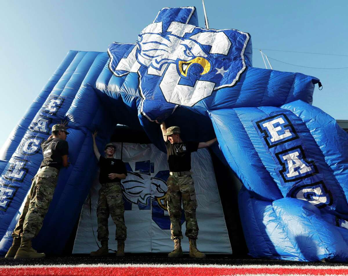 New Caney JROTC member Joshua Callaway, center, helps hold up the team's inflatable tunnel before a high school football game at Randall Reed Stadium, Friday, Sept. 3, 2021, in New Caney.
