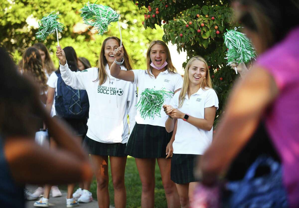 Seniors Chelsea Hyland, left, Kate Hong, center, and Caroline Nemec welcome underclassmen on the first day of school at Sacred Heart Greenwich in Greenwich, Conn. Wednesday, Sept. 8, 2021. Sacred Heart and other Greenwich private schools began their 2021-2022 school year on Wednesday, a week after Greenwich Public Schools.