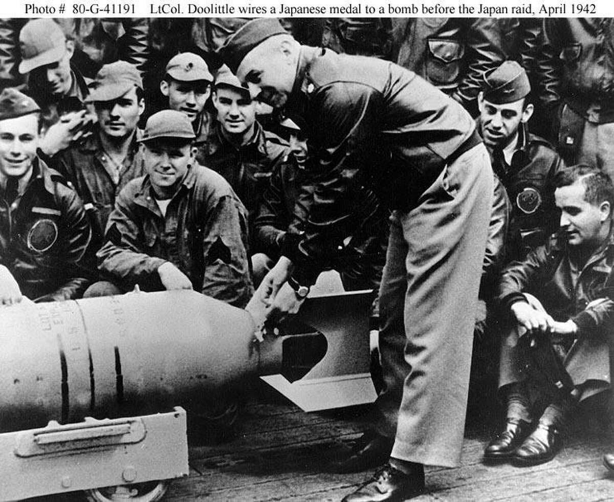 Lt. Col. Jimmy Doolittle, leader of the raiding force, wires a Japanese medal to a 500-pound bomb during ceremonies on the flight deck of the USS Hornet shortly before taking off for Japan.