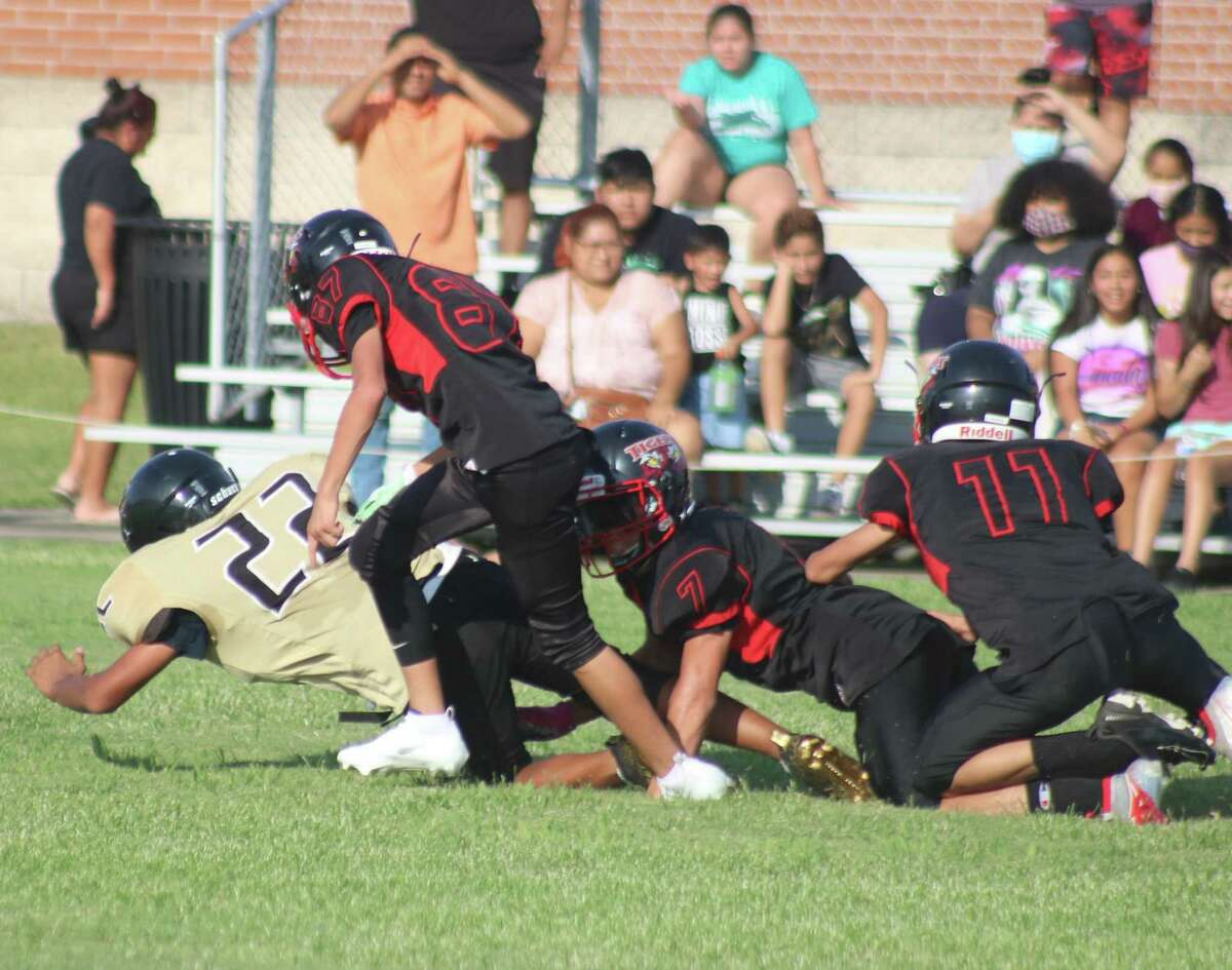 Miller Intermediate's Lazaro Obiegan (22) drags several San Jacinto Intermediate defenders with him during Tuesday's season opener for the seventh graders. Obiegan finished with 133 yards and three TDs during the 20-19 defeat.