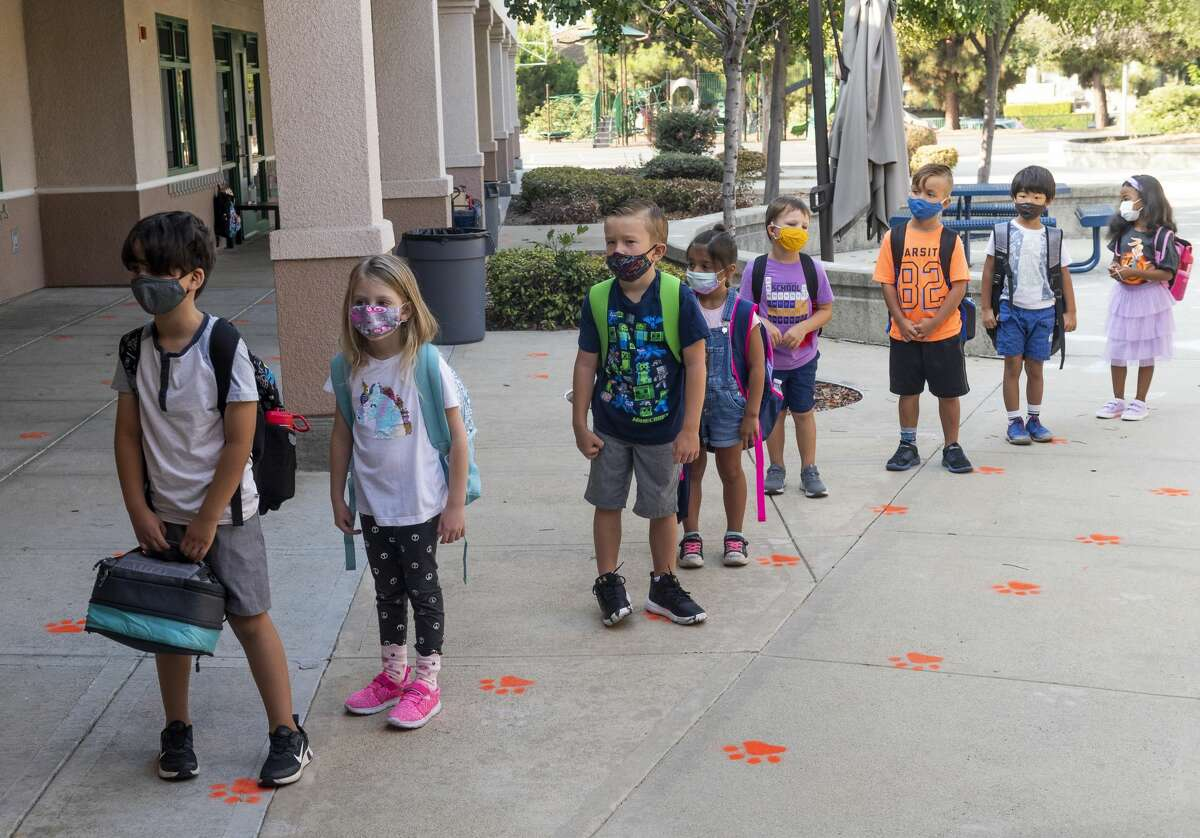 Masked students wait in line for the first day of school at Tustin Ranch Elementary School in Tustin, CA. (Photo by Paul Bersebach/MediaNews Group/Orange County Register via Getty Images)
