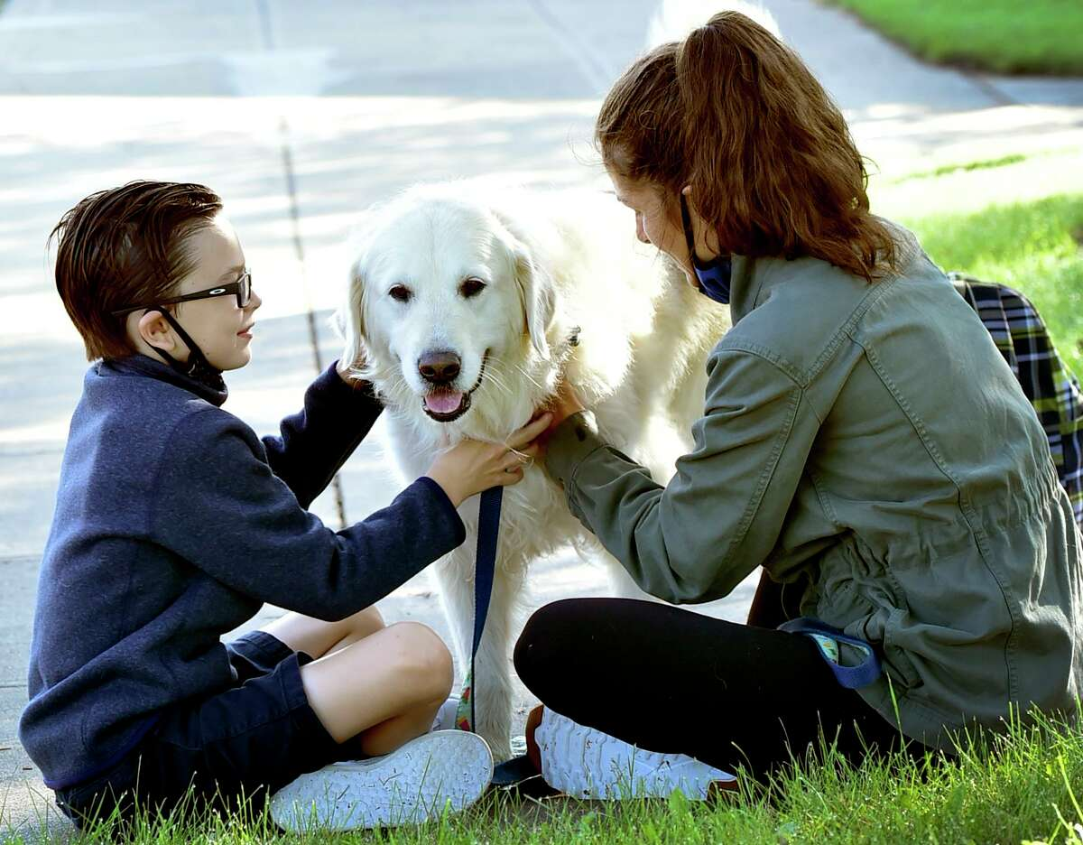 Guilford, Connecticut - September 08, 2021: Russell Clune, 9, his dog Bailey, and mother Holly Clune wait for the start of his first day of school as a fourth-grader at Melissa Jones Elementary School in Guilford.