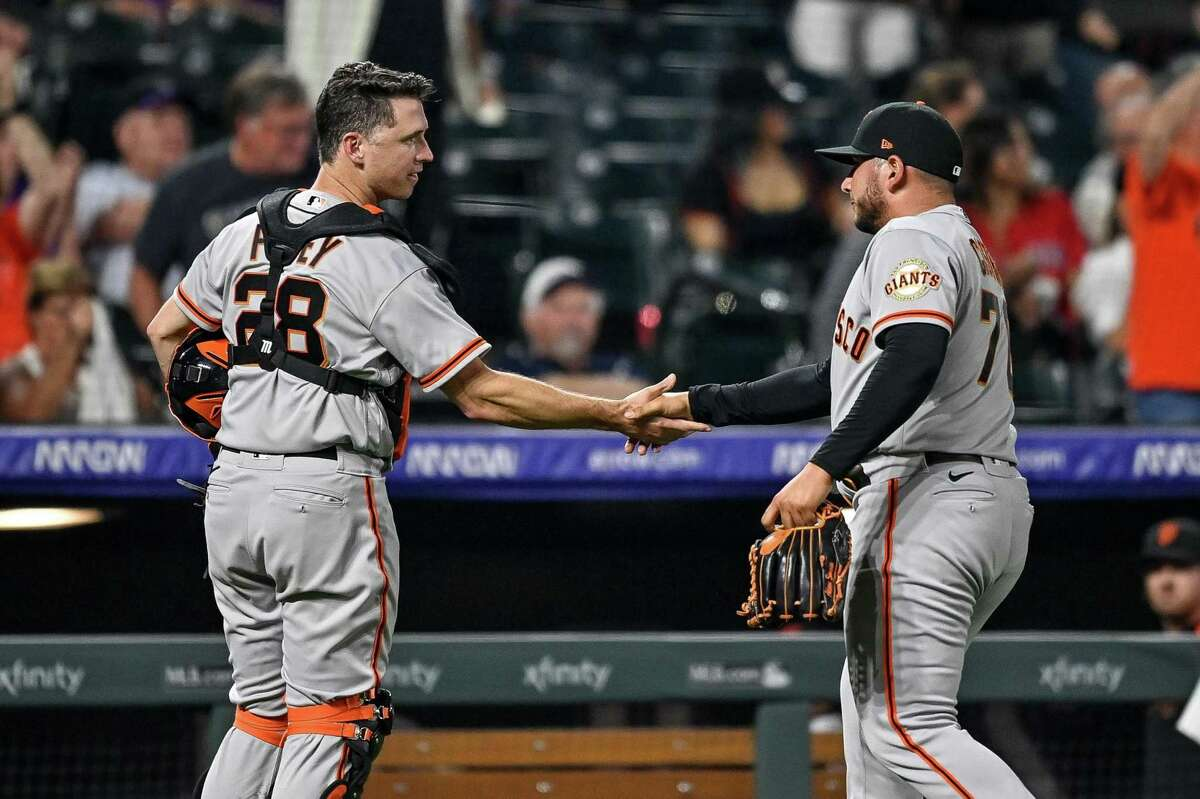 DENVER, CO - SEPTEMBER 7: Kervin Castro #76 of the San Francisco Giants is congratulated by Buster Posey #28 after a scoreless eighth inning in Castos Major League debut against the Colorado Rockies at Coors Field on September 7, 2021 in Denver, Colorado. (Photo by Dustin Bradford/Getty Images)