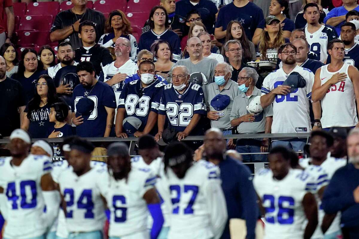 Dallas Cowboys fans and players stand for the national anthem prior to an NFL preseason football game against the Arizona Cardinals, Friday, Aug. 13, 2021, in Glendale, Ariz. (AP Photo/Ross D. Franklin)