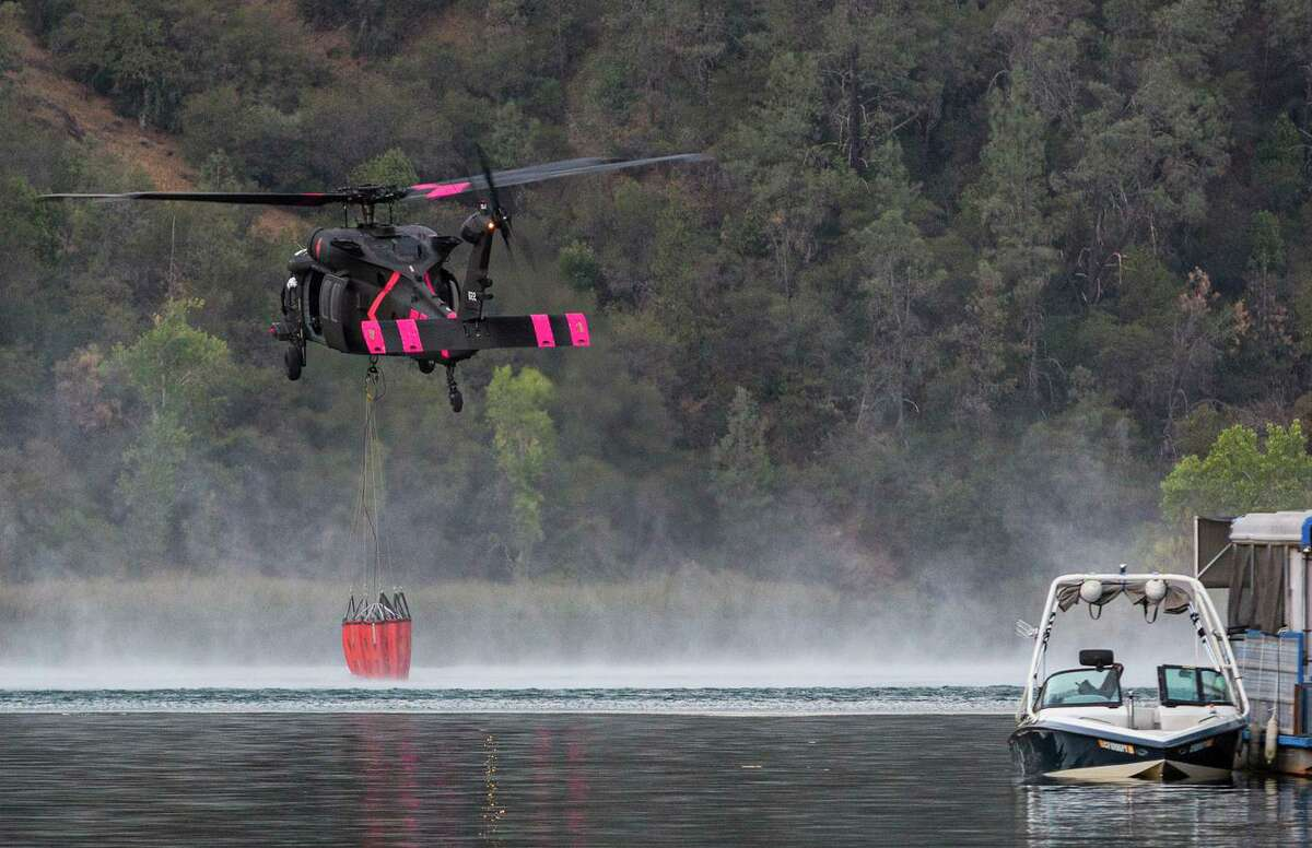 A Black Hawk helicopter uses Lake Clementine to collect water to drop on the Bridge Fire, burning around the Foresthill Bridge in Auburn (Placer County) on Sunday.
