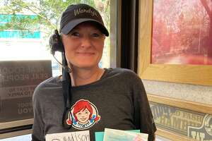 Kelly Brady, a coworker of Deborah Carpenter, holds up a card signed by the Wendy's crew and a drawing from Brady's granddaughter. Carpenter once entertained the granddaughter at the store while Brady worked. Now Carpenter is unconscious after a bike accident and police are looking for witnesses to the incident.