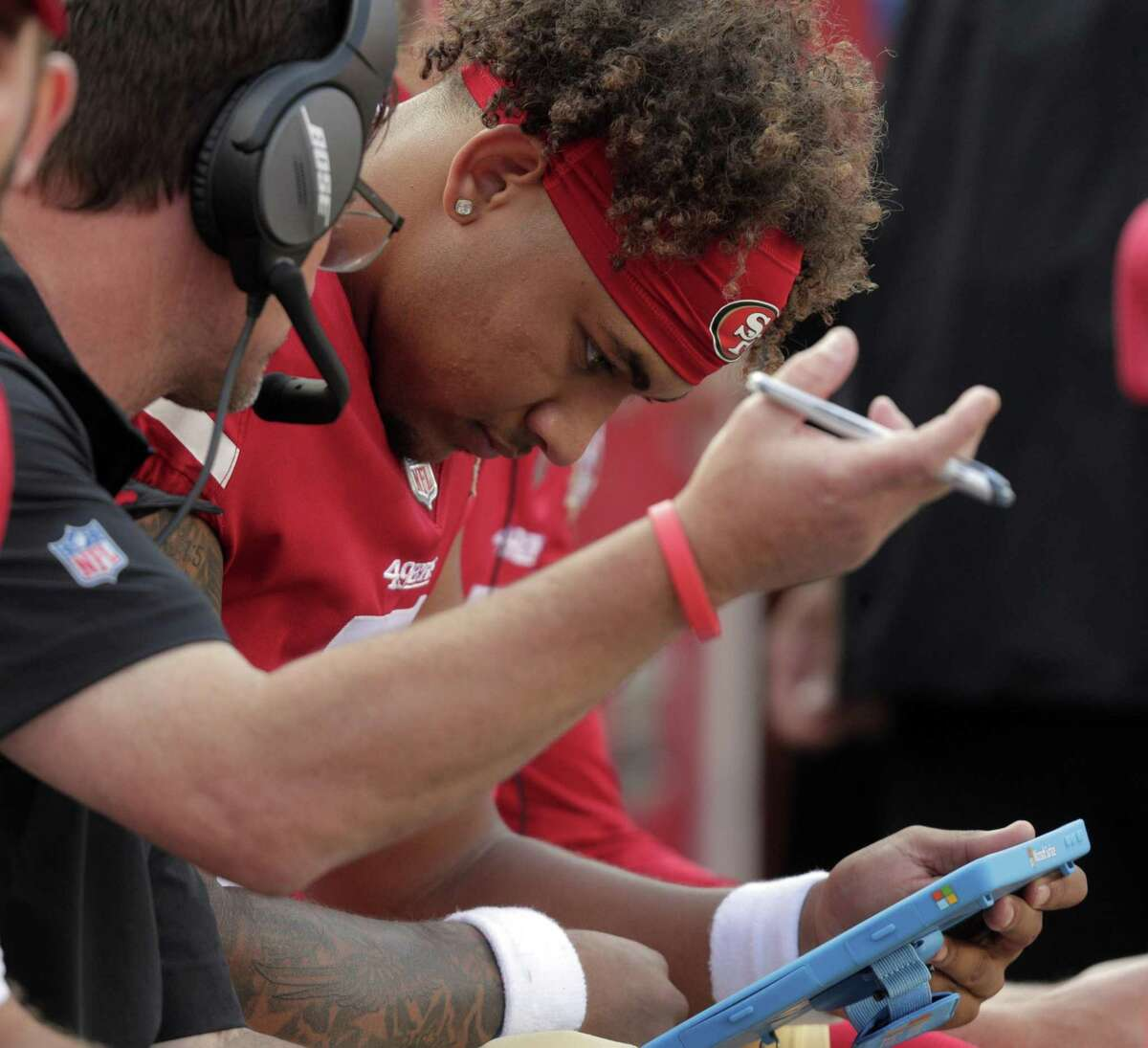 Trey Lance (5) talks with quarterbacks coach Rich Scangarelo on the bench after getting sacked and the 49ers punted in the first half as the San Francisco 49ers played the Kansas City Chiefs at Levi's Stadium in Santa Clara, Calif., on Saturday, August 14, 2021.