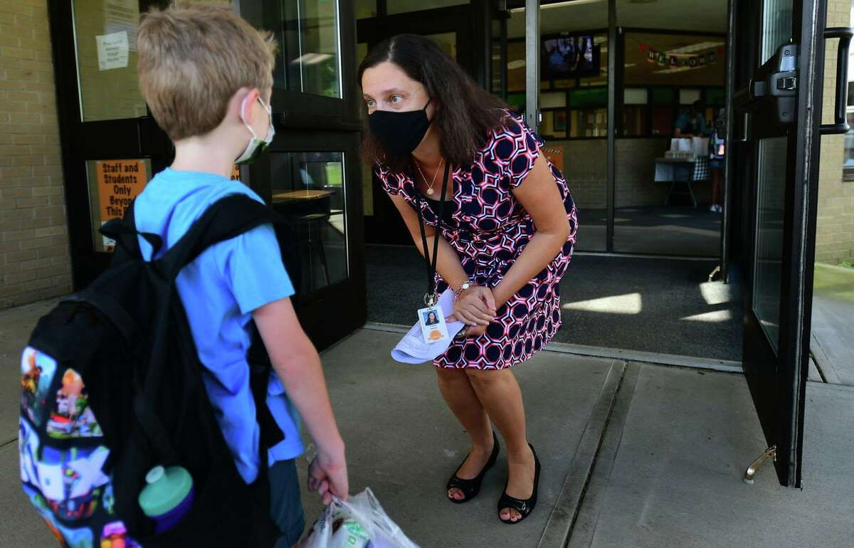 Students are greeted by staff including principal Andrea D'Auito as they arrive for their first day of class at Long Hill Elementary School on Wednesday in Shelton.