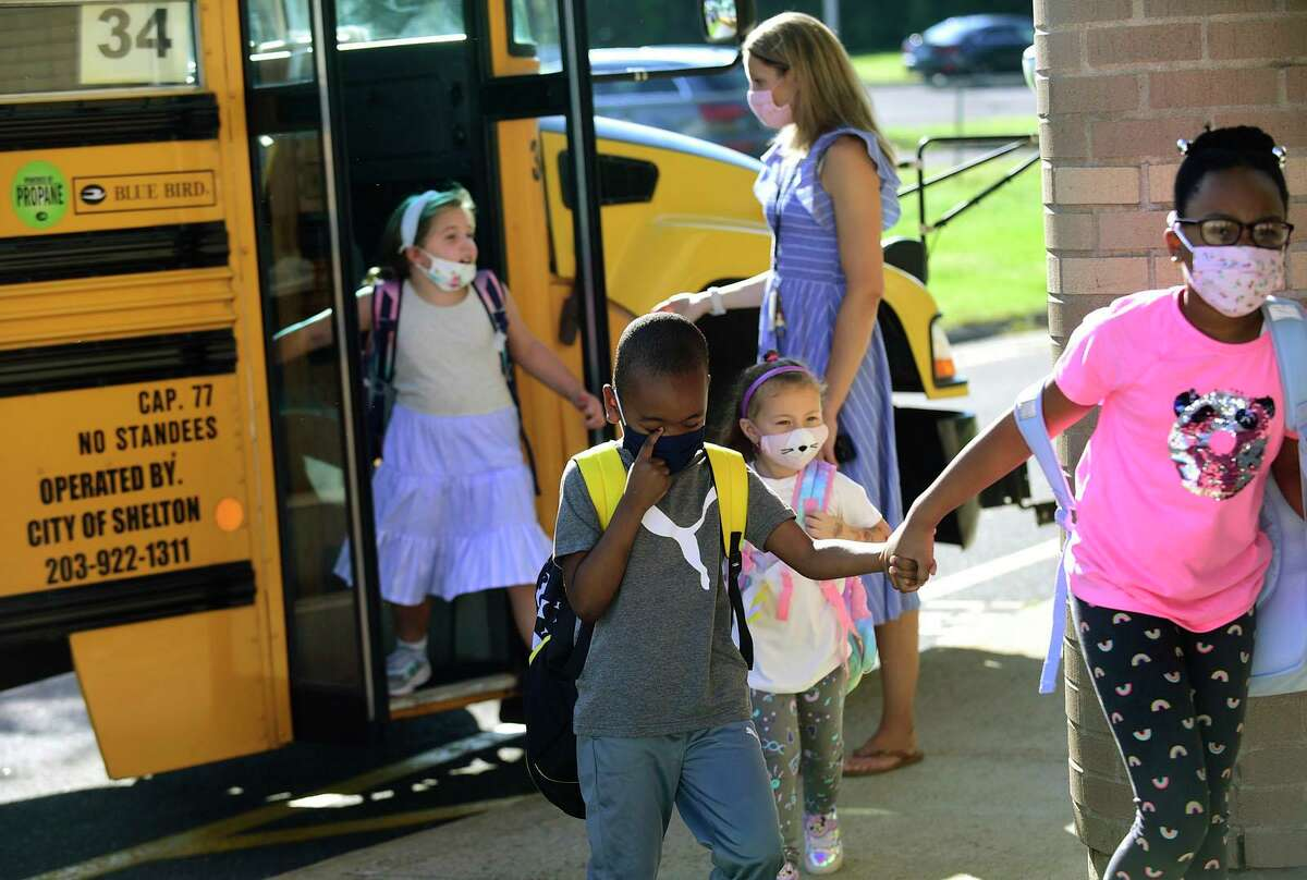 Students are greeted by staff as they arrive for their first day of class at Long Hill Elementary School Wednesday, September 8, 2021, in Shelton, Conn.