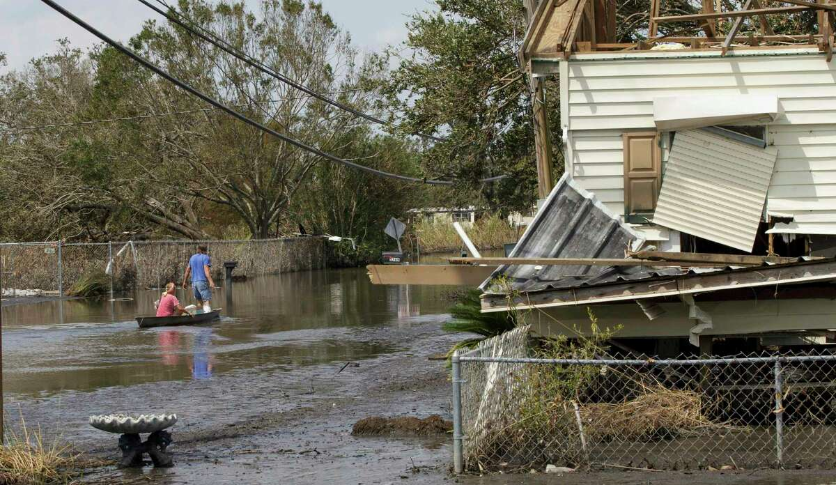 Lower Lafitte, La., residents head to their residence to continue cleaning Tuesday, Sept. 7, 2021, in the aftermath of Hurricane Ida. (David Grunfeld/The Times-Picayune/The New Orleans Advocate via AP)