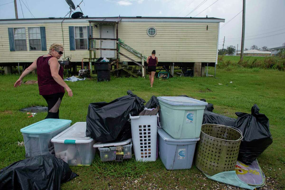 Opal Watkins, left, walks past a past a pile of trash as she follows Sandy Gilbert, center, into her home in Plaquemines Parish, La., Tuesday, Sept. 7, 2021. Both Watkins and Gilbert have been battling mold growth in their respective homes, a week after Hurricane Ida. (Chris Granger/The Times-Picayune/The New Orleans Advocate via AP)