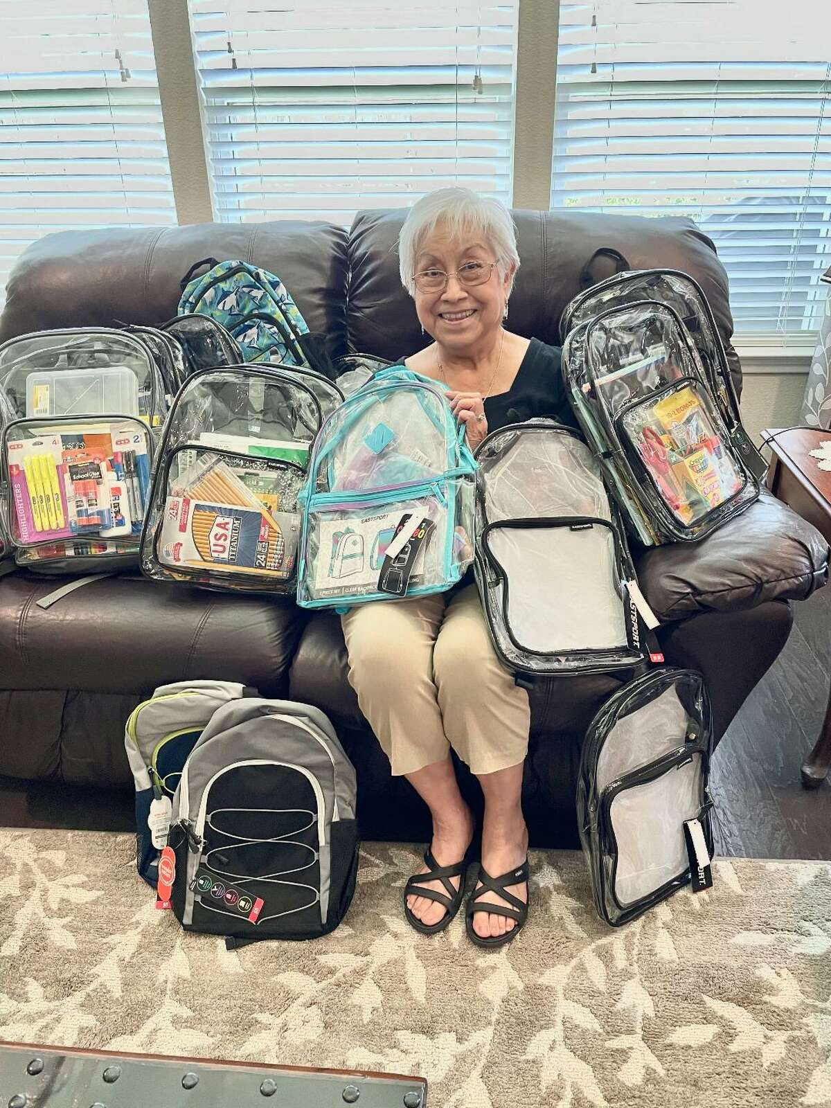 Loraine Gomez, service chair for Beta Sigma Pi's Theta Master chapter, organizes school supplies and backpacks collected for children at the Resource and Crisis Center of Galveston County shelter. For Theta Master membership information, contact Judy Hotman, 713-724-3154.