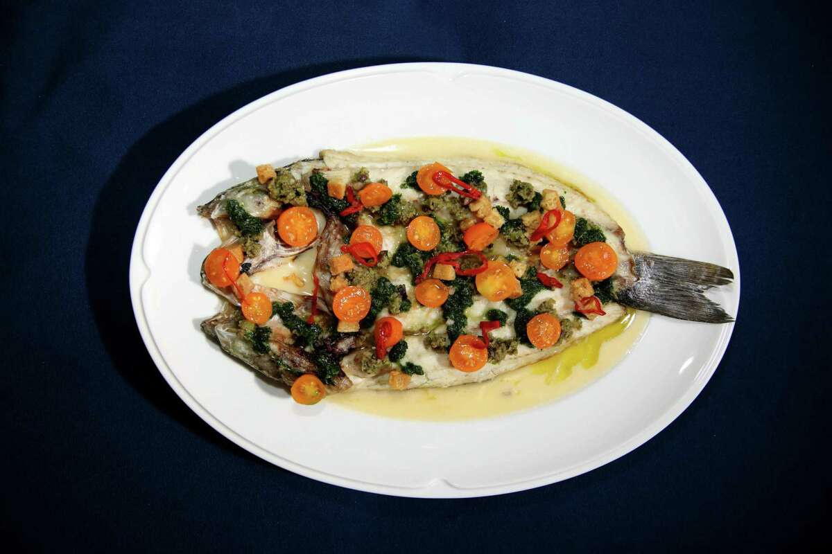 A plate of whole grilled branzino includes fennel beurre blanc and panzanella vinaigrette at Mama.