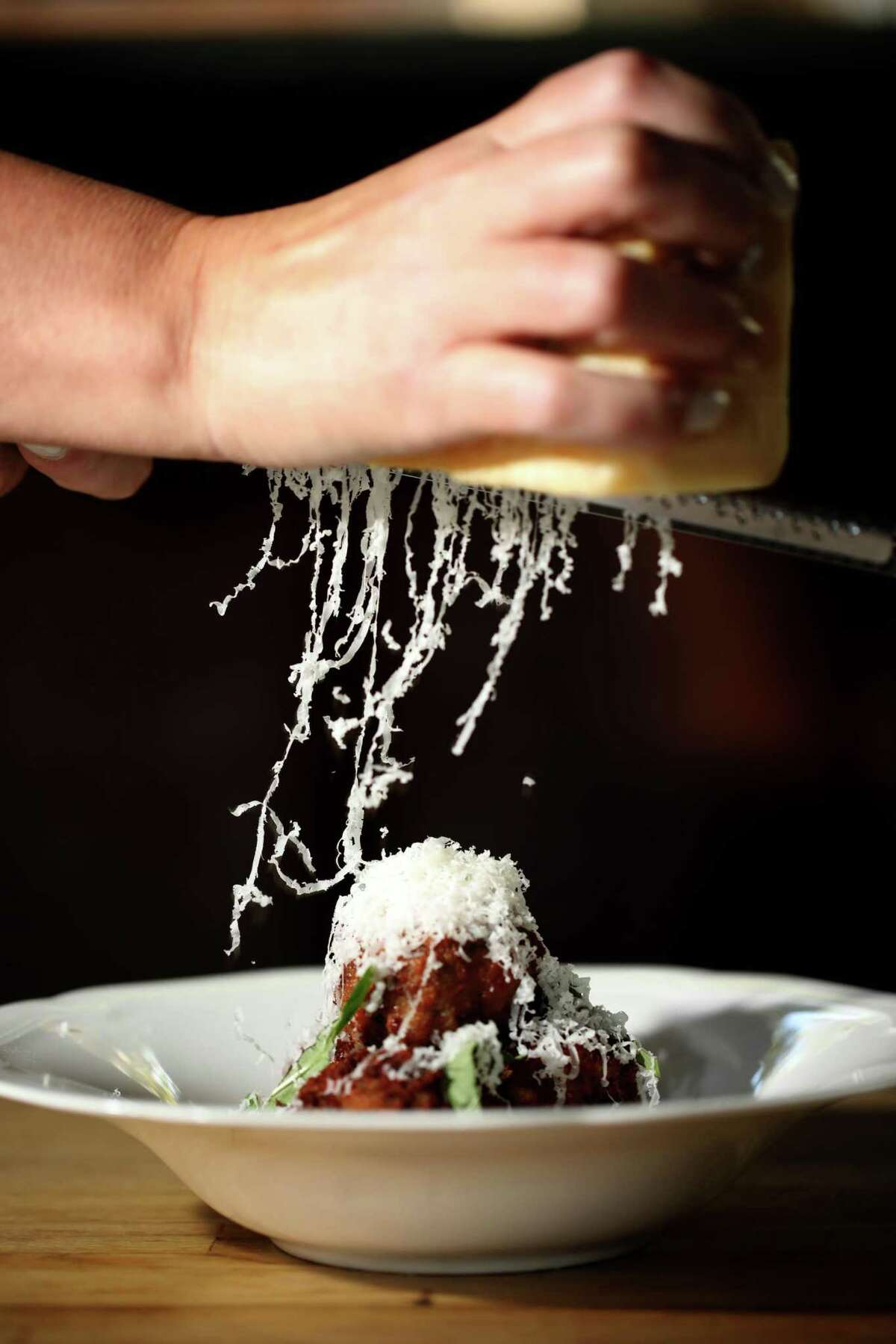 Chef Priscilla Przygocki grates cheese atop of the pan-fried beef and pork meatballs.